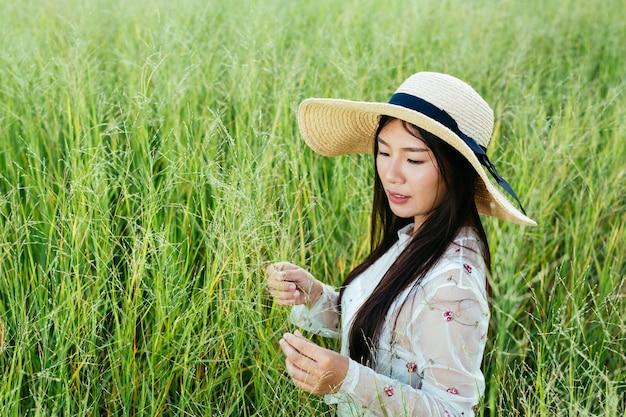 Een mooie vrouw die gelukkig in het grasland zit.