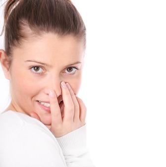 Een mooie vrouw die haar mond bedekt met een hand op een witte achtergrond