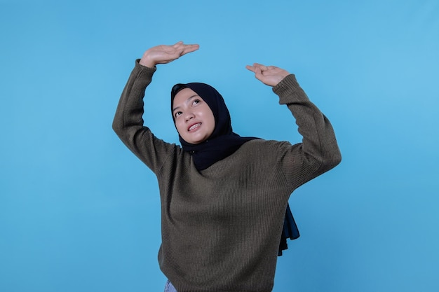 Een mooie vrouw die hijab draagt, steekt haar hand op en voelt zwaar op de blauwe muur