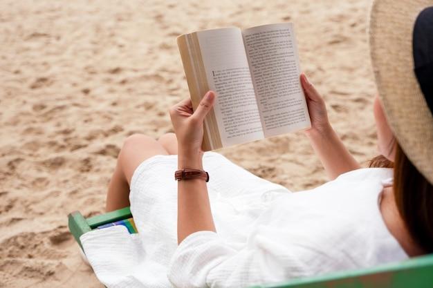 Een mooie vrouw die ligt en een boek leest op de strandstoel met een ontspannen gevoel