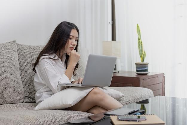 Een mooie vrouw die thuis met een laptop en tabletcomputer werkt.