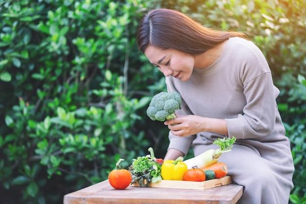 Een mooie vrouw die verse gemengde groenten plukt en controleert van een houten dienblad op tafel