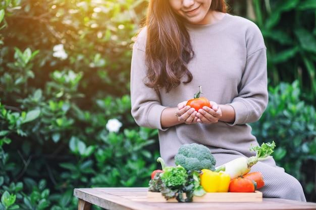 Een mooie vrouw die verse gemengde groenten vasthoudt en plukt uit een houten dienblad op tafel