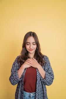 Een mooie vrouw die zich kalm voelt met haar ogen gesloten met een handgebaar terwijl ze de borst vasthoudt terwijl ze...