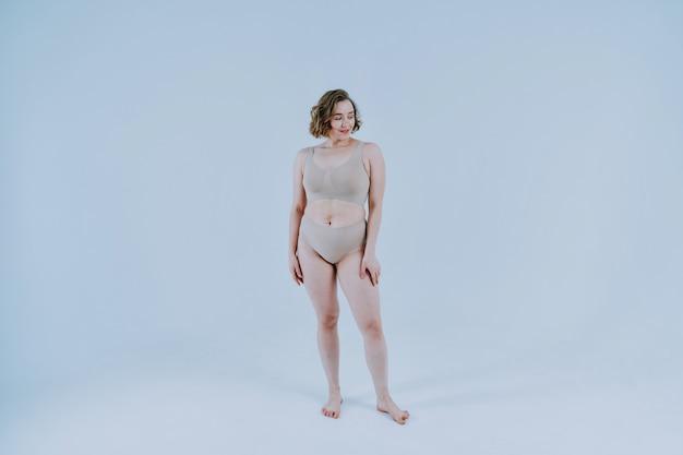 Een mooie vrouw die zich voordeed in de studio die lingerie draagt. concept over lichaamspositiviteit en zelfacceptatie