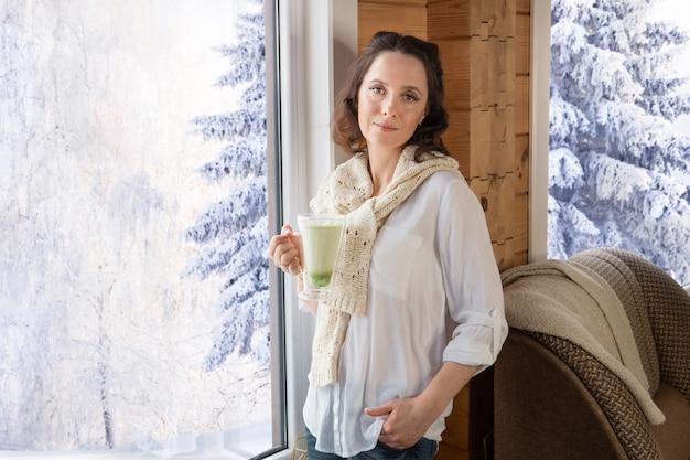 Een mooie vrouw drinkt een drankje met marshmallows bij het raam