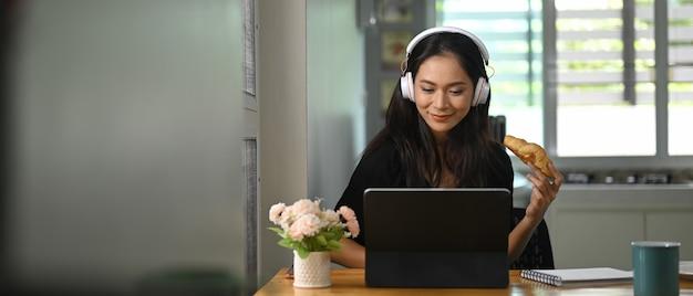 Een mooie vrouw eet een croissant terwijl ze een computertablet gebruikt aan het houten bureau.