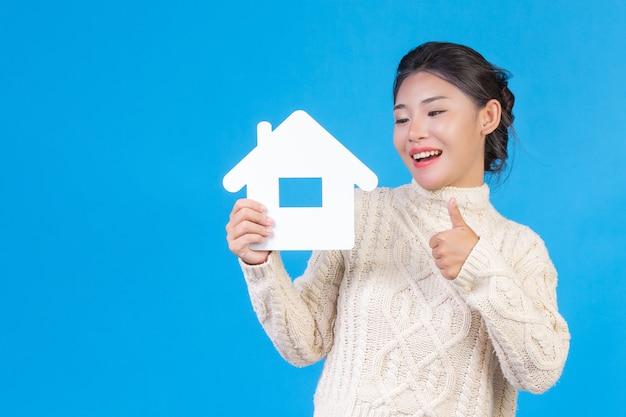 Een mooie vrouw, gekleed in een nieuw wit shirt met lange mouwen en een huissymbool. huizenhandel.