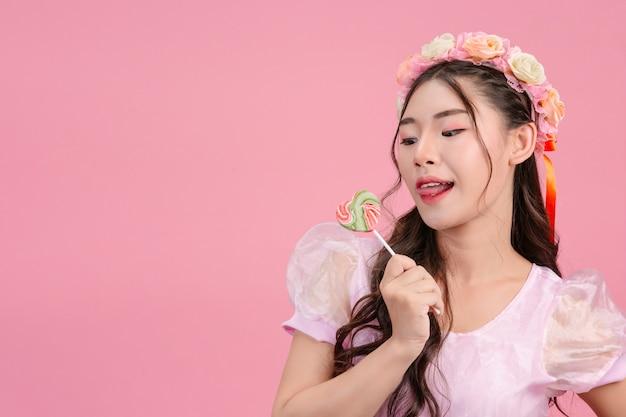 Een mooie vrouw gekleed in een roze prinses speelt met haar zoete snoep op een roze.