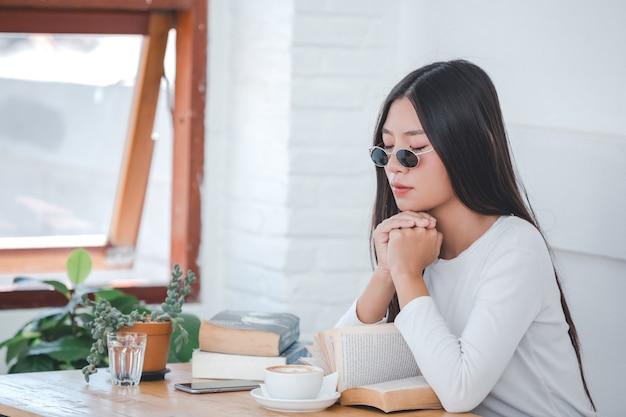 Een mooie vrouw, gekleed in een wit shirt met lange mouwen in een koffieshop