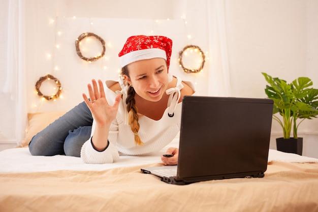 Een mooie vrouw glimlacht en zwaait met haar hand naar haar laptop. een meisje met een rode hoed met kerstmis feliciteert haar familieleden via een videoverbinding.