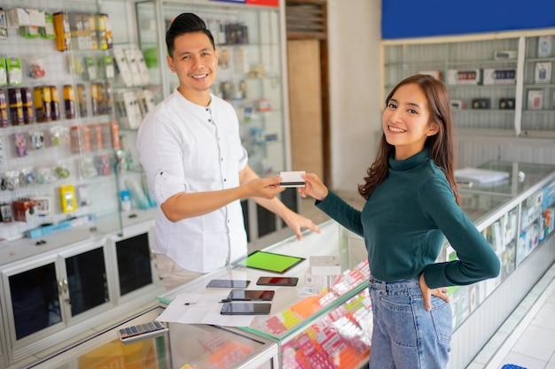 Een mooie vrouw glimlacht terwijl ze een creditcard aan een man geeft tijdens het betalen