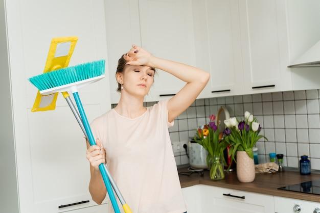 Een mooie vrouw houdt een dweil en een borstel voor het schoonmaken en dweilen in haar handen en zucht van vermoeidheid. een huisvrouw staat in de keuken en veegt het zweet van haar gezicht