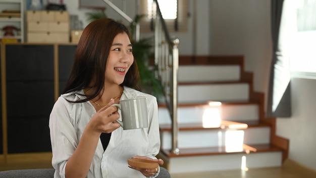 Een mooie vrouw houdt thuis een kopje koffie en glimlacht