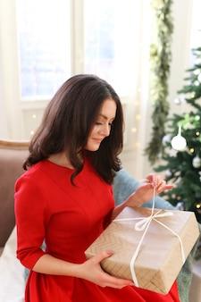 Een mooie vrouw in een felrode jurk viert kerstmis in een gezellig huis versierd met een boom