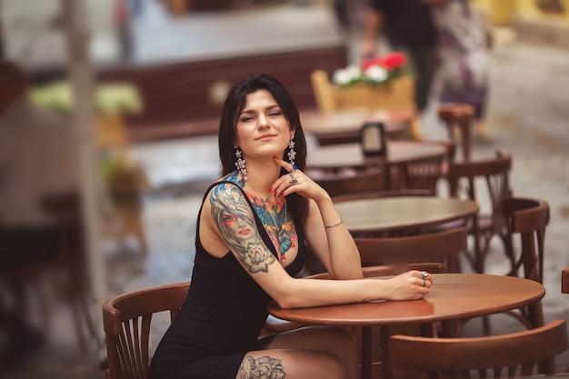 Een mooie vrouw in een gele jurk, tatoeages, zit in het café. buitenshuis