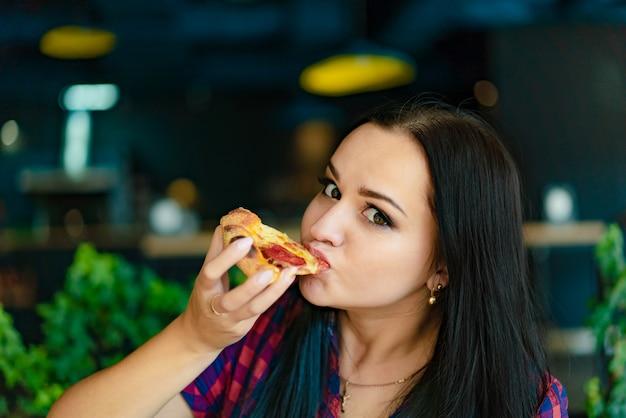 Een mooie vrouw in een geruit hemd houdt een plak pizza in haar hand en eet het in een pizzeria.