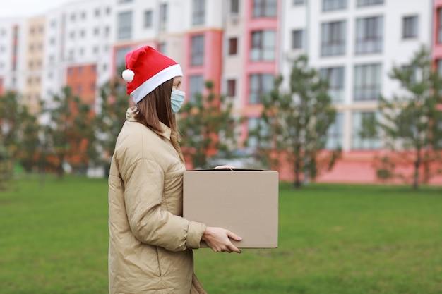 Een mooie vrouw in een rode kerstman-hoed en een medisch beschermend masker houdt een grote doos buiten