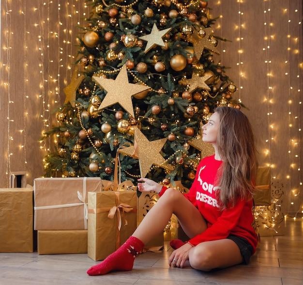 Een mooie vrouw in een rode trui zit te wachten op een vakantie in de buurt van de nieuwjaarsboom versierd met gouden slingers en kerstversieringen. het idee en concept van kerstmis en nieuwjaar