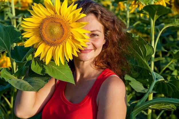 Een mooie vrouw in een rood t-shirt houdt een grote bloem van een zonnebloem vast.