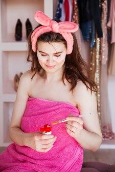 Een mooie vrouw in een roze handdoek en met een cosmetisch verband op haar hoofd gaat een cosmetisch masker uitknijpen