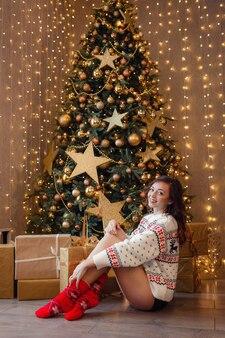 Een mooie vrouw in een witte trui zit te wachten op een vakantie in de buurt van de nieuwjaarsboom versierd met gouden slingers en kerstversieringen. het idee en concept van kerstmis en nieuwjaar