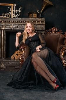 Een mooie vrouw in een zwarte jurk met een korset zittend op een stoel in rode schoenen