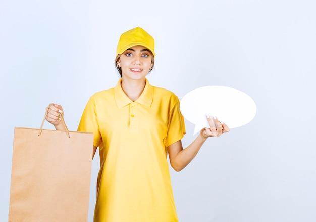 Een mooie vrouw in geel uniform met bruine lege ambachtelijke papieren zak en lege tekstballon.