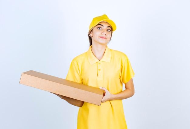 Een mooie vrouw in geel uniform met een bruine lege doos van ambachtelijk papier.