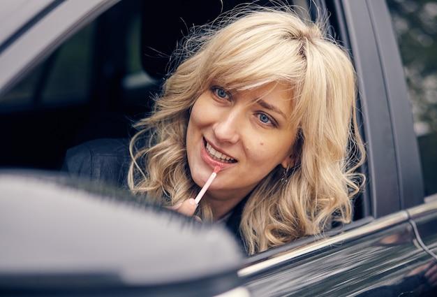 Een mooie vrouw in het autoraam trekt haar lippen