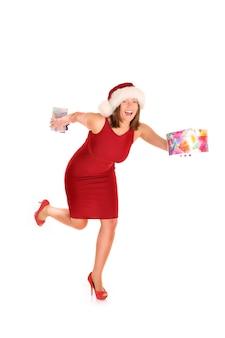 Een mooie vrouw in het kostuum van de kerstman die met cadeautjes op een witte achtergrond loopt
