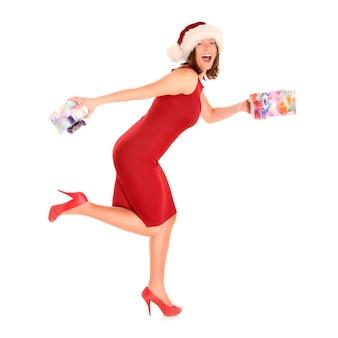 Een mooie vrouw in het kostuum van de kerstman die met cadeautjes over wit rent