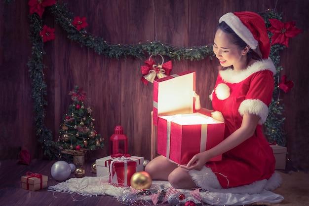 Een mooie vrouw in kerstman-kostuum was opgetogen toen ze de geschenkdoos opende op prettige kerstdagen en een gelukkig nieuwjaarsdag.