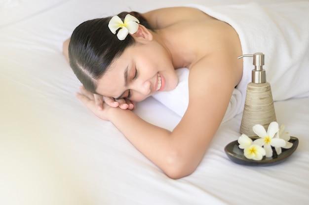 Een mooie vrouw is ontspannend en heeft massage in het kuuroord, massage en schoonheidsbehandeling concept.