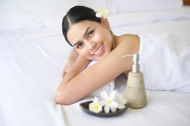 Een mooie vrouw is ontspannend en heeft massage in kuuroord