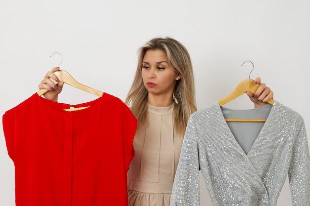 Een mooie vrouw kan niet kiezen voor een jurk op een witte achtergrond welke jurk kiezen zilver of rood?