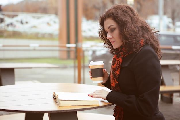 Een mooie vrouw leest een boek op het terras van een caféwinkel