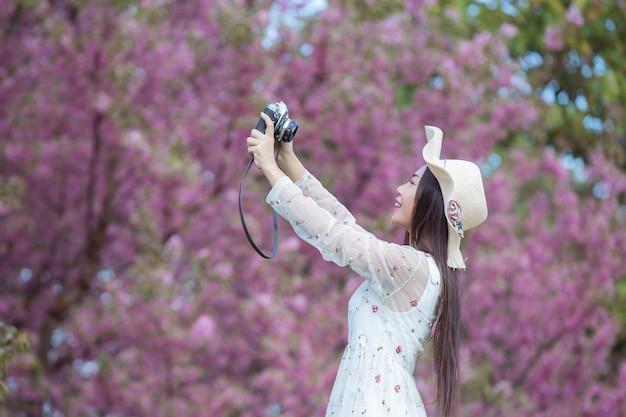 Een mooie vrouw maakt een foto met een filmcamera in de bloementuin van sakura.