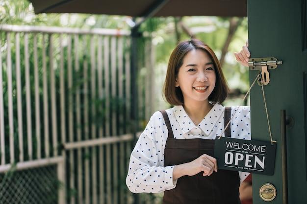 Een mooie vrouw met een bedrijfsteken met de tekst 'welkom, we zijn open' in de koffiewinkel of de restaurantdeur