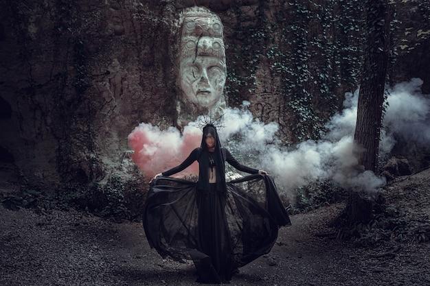 Een mooie vrouw met een bleke huid in een zwarte jurk en in de zwarte kroon. gotische look. outfit voor halloween. een vrouw met gekleurde rook tegen het beeld van een afgod