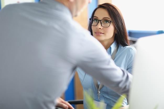 Een mooie vrouw met een bril zit in een kantoor en kijkt naar een man. de baas en de officemanager communiceren nauw