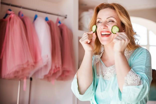 Een mooie vrouw met een kamerjas en met stukjes komkommer op haar gezicht glimlacht en kijkt uit het raam. thuis huidverzorging en natuurlijke cosmetica concept.