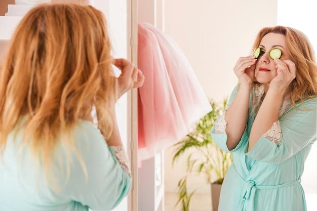 Een mooie vrouw met een kamerjas en plakjes komkommer voor haar ogen staat voor de spiegel. thuis huidverzorging en natuurlijke cosmetica concept.