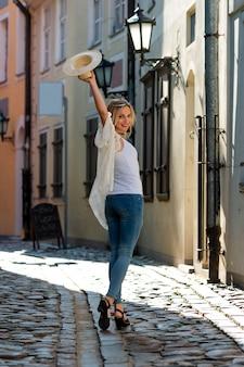 Een mooie vrouw met een lichte hoed, met lang blond haar, een witte blouse en blauwe jeaans in het midden van de oude stadsstraat