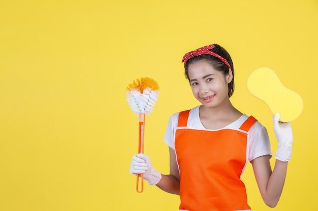 Een mooie vrouw met een reinigingsapparaat op een geel