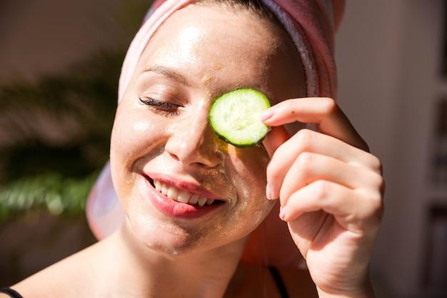 Een mooie vrouw met een roze handdoek over haar hoofd en met een stukje komkommer op haar oog
