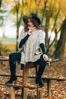 Een mooie vrouw met een zwarte hoed zit op een tafel