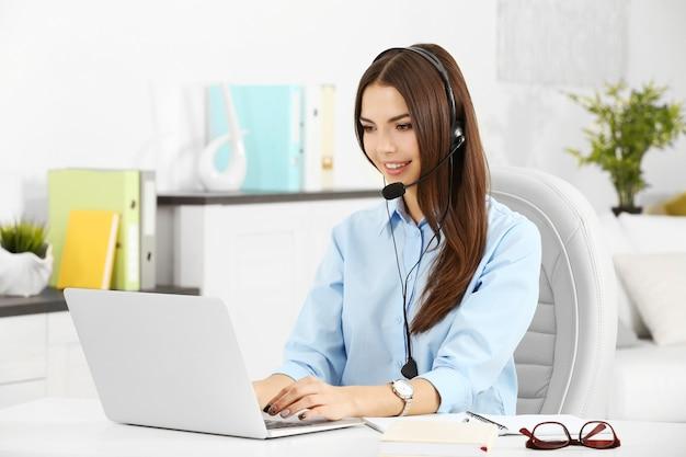 Een mooie vrouw met koptelefoon en microfoon die op kantoor werkt