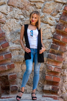 Een mooie vrouw met lang blond haar, een witte blouse en blauwe jeaans bij de stenen muur van de oude stad
