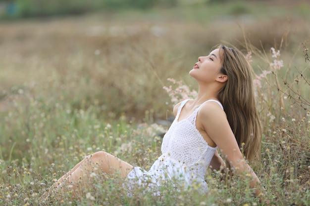 Een mooie vrouw met lang haar in een jurk zittend op een weiland en bloemen in het avondlicht.
